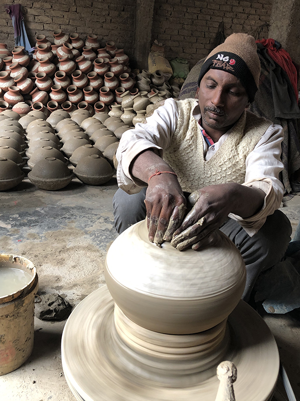 Jagmohan creates the neck of a water jar at his pottery production business in Uttam Nagar, India, near New Delhi. / Ceramics Monthly photo