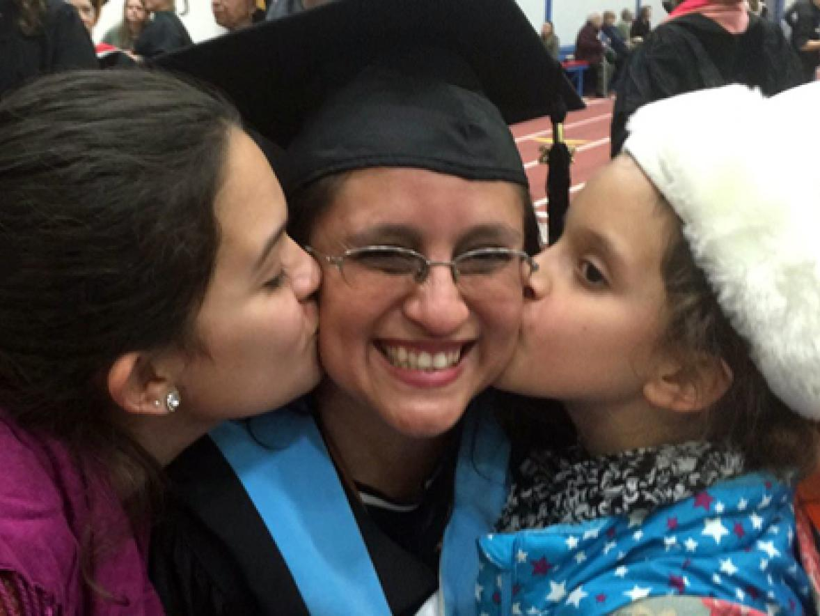 Online student Veronica Solano receives a congratulatory kiss after commencement from daughters, Nasim, left, and Anisa.