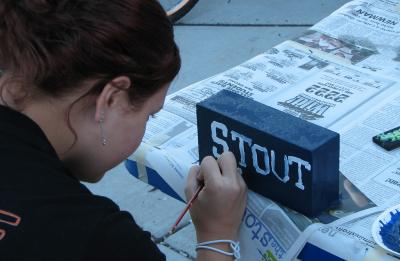 Student painting STOUT on a brick