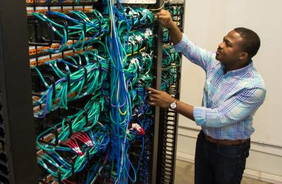 Emmanuel Mbanali in the telecom/network room at the UW-Stout Admin Building.
